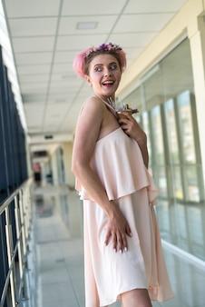 大きなビジネスセンター内でポーズをとって茶色の服を着たかわいい裸足の女性