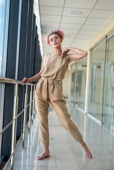建物の中に立って楽しみにしているかわいい裸足の女性