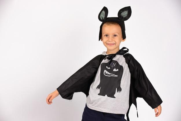 Милая летучая мышь улыбается и счастлива готовится к хэллоуину. красивый кавказский мальчик детского сада. фото на белой стене.