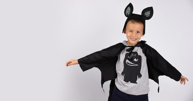 Cute bat smiling and happy preparing for halloween. handsome caucasian kindergarden boy. photo on a white wall.