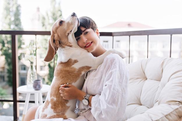 Милая собака породы бигль обнимает черноволосую девушку, чтобы выразить верность