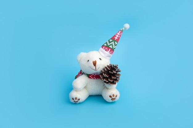 Милый мишка в игрушечной новогодней шапке держит в лапках шишку.