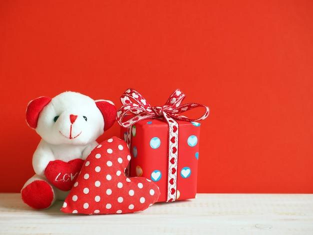 Милый медведь с текстильным сердцем и подарочной коробкой на красном фоне
