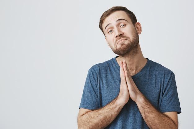 Cute bearded man asking help, pleading gesture