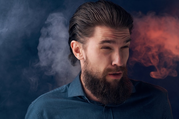 Cute bearded man in shirt and smoke fashion dark background