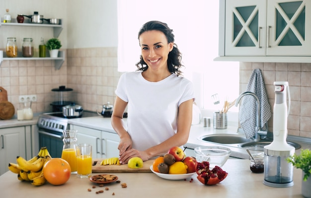 Милая красивая и счастливая молодая брюнетка женщина на кухне дома измельчает фрукты