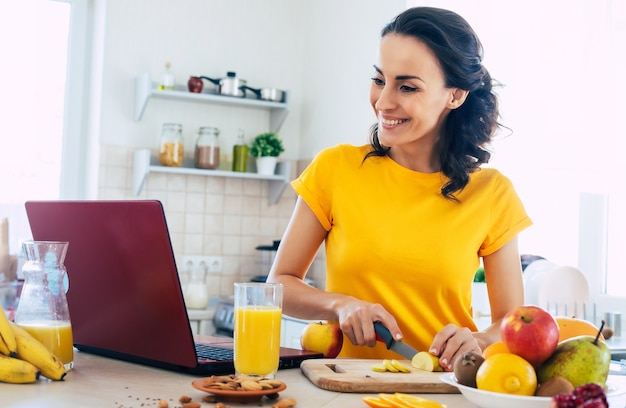 Милая красивая и счастливая молодая брюнетка женщина на кухне дома готовит фруктовый салат