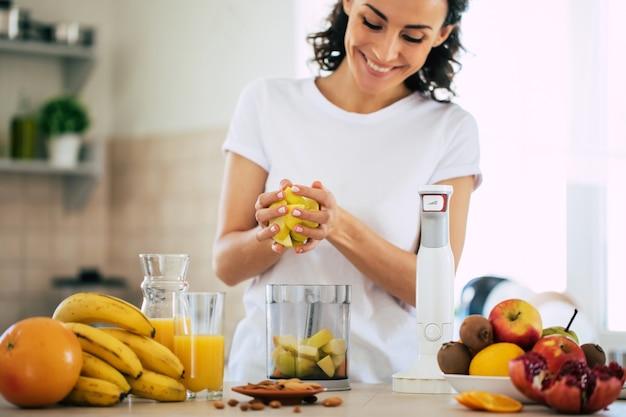 Милая красивая и счастливая молодая брюнетка женщина на кухне дома готовит фруктовый веганский салат или здоровый смузи и веселится