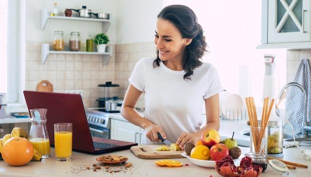 Милая красивая и счастливая молодая брюнетка женщина на кухне дома готовит фруктовый веганский салат