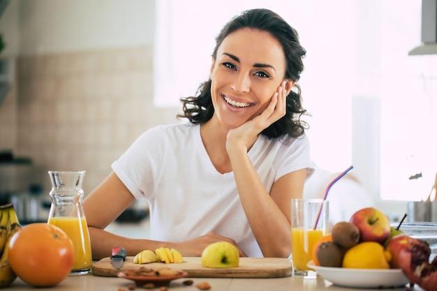 Милая красивая и счастливая молодая брюнетка женщина на кухне