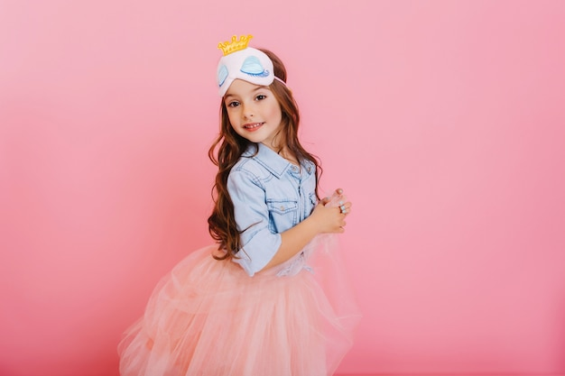 Cute beautiful carnival kid having fun isolated on pink background. pretty little girl with long brunette hair, in tulle skirt, princess mask expressing happiness to camera, celebrating children party