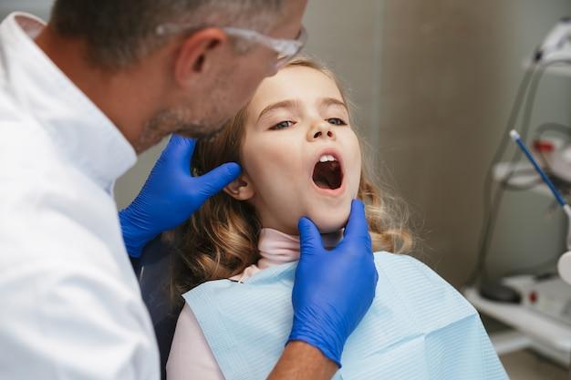 Cute beautiful child girl sitting in medical dentist center