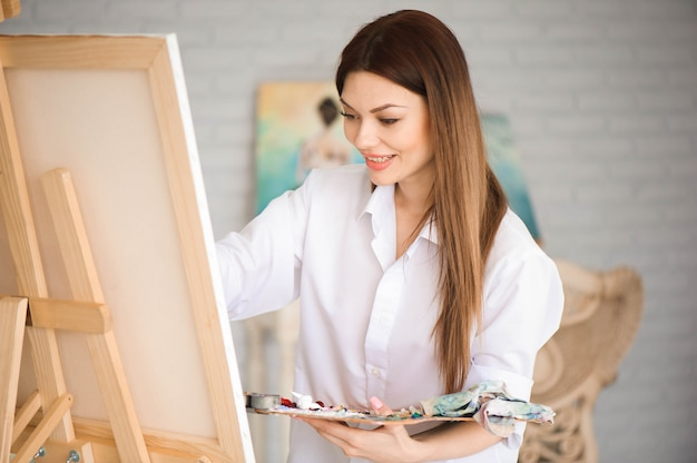 Cute beautiful girl artist painting a picture on a canvas on an easel. long hair, brunette. holding colorful brush and palette.