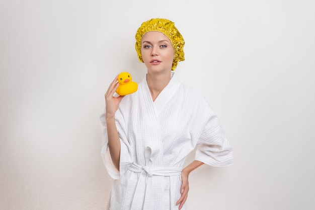 Cute beautiful girl in a bathrobe and a yellow shower cap on her head poses on a white background holding a small yellow rubber duck. the concept of hygiene and cleanliness.