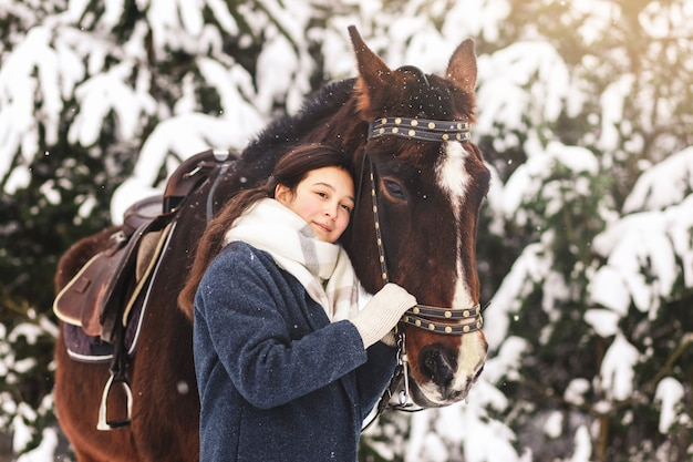 A cute beautiful girl cuddles up to a horse in winter in the park. love and care for horses.