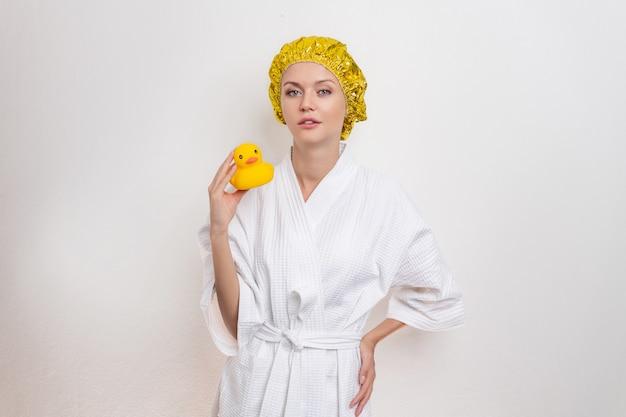 Симпатичная красивая девушка в халате и желтый шапочка для душа на голове позирует на белом фоне, держа маленький желтый резиновая утка. понятие гигиены и чистоты.