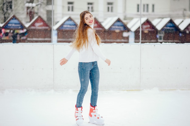 Cute and beautiful girl in a white sweater in a winter city