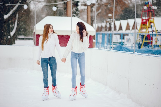 Cute and beautiful girls in a white sweater in a winter city