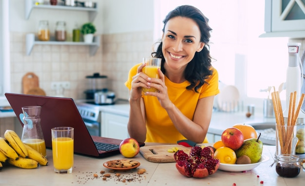 Cute beautiful and happy young brunette woman in the kitchen at home is preparing fruit salad