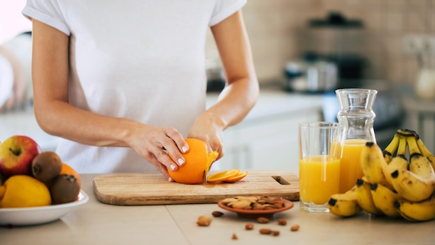 Cute beautiful and happy young brunette woman in the kitchen at home is preparing orange juice