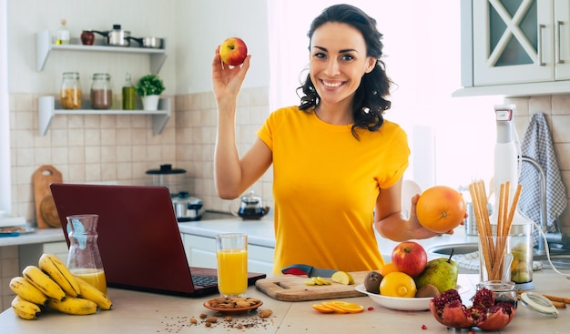 Cute beautiful and happy young brunette woman in the kitchen at home with fruits and laptop computer