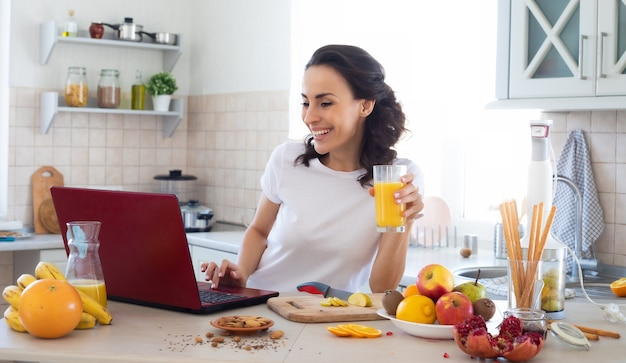 Cute beautiful and happy young brunette woman in the kitchen is using the laptop