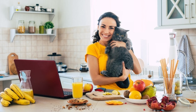 Cute beautiful and happy young brunette woman with her cat in the kitchen at home