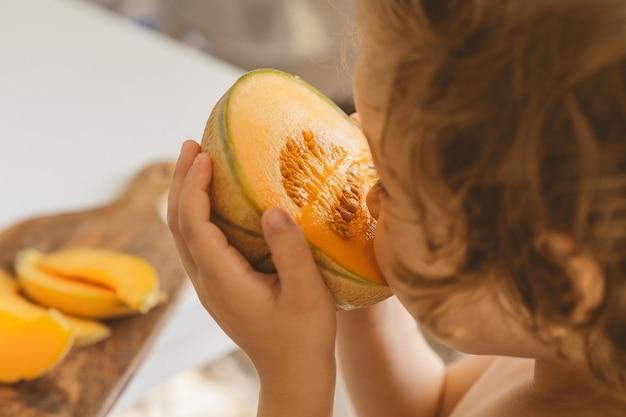 Милый красивый маленький мальчик ест свежую дыню.