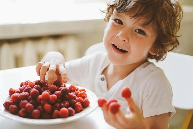 新鮮なラズベリーを食べてかわいい美しい男の子。健康食品、小児期および発達。