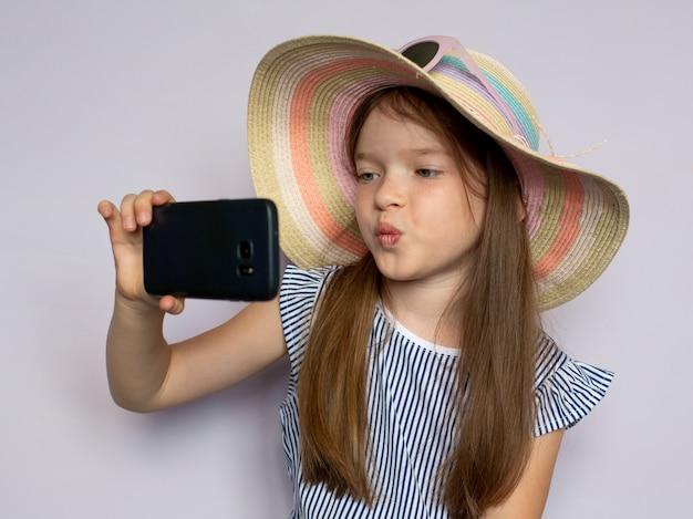Милая красивая маленькая девочка в платье и шляпе фотографирует делает селфи на смартфон