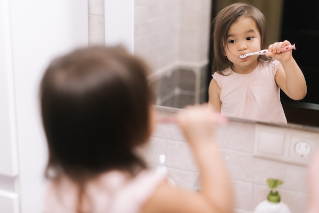 Милая красивая маленькая девочка чистит зубы зубной щеткой перед зеркалом в ванной