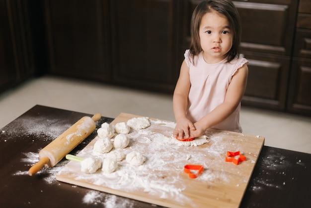 귀여운 아름다운 소녀가 쿠키 형태로 반죽을 자르고 있습니다