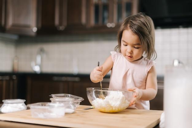 Милая красивая маленькая девочка месит и смешивает творог и яйца в прозрачной миске