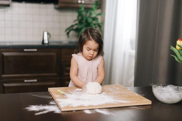 귀여운 아름다운 소녀가 식탁에서 쿠키를 굽기 위해 반죽을 준비합니다
