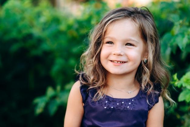 側面を見て笑っているかわいい、美しい、小さな女の子 Premium写真
