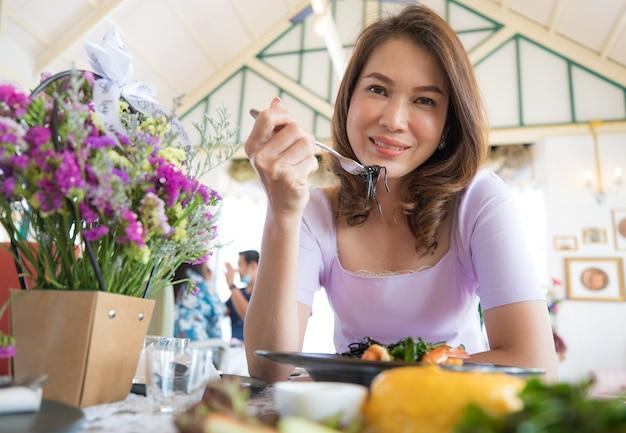 Милая красивая азиатская женщина средних лет сидит за столом в ресторане и ест спагетти