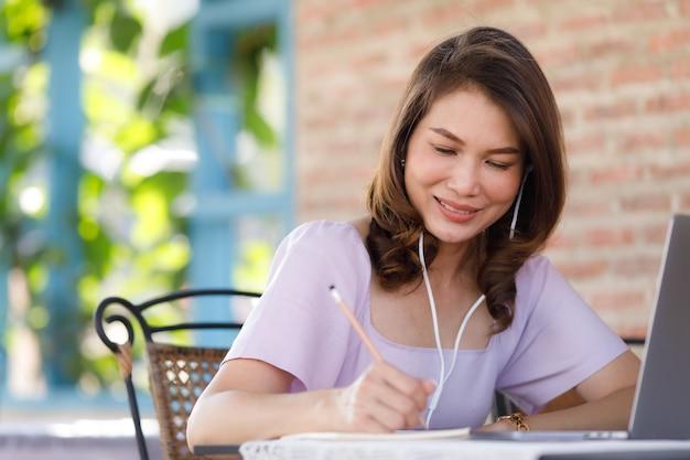 店に座って、ラップトップコンピューターで紙のノートに書くために鉛筆を使用してかわいい美しい中年アジアの女性