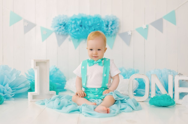 A cute beautiful one-year-old boy is celebrating his first birthday.photo zone for the holiday