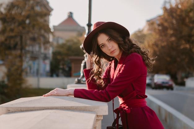 Милая красивая стильная женщина в фиолетовом костюме гуляет по городской улице, модная тенденция сезона весна-лето-осень в шляпе, держа кошелек