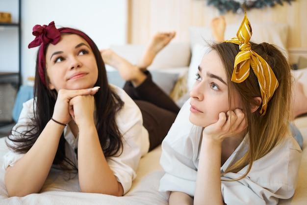 Carine belle ragazze adolescenti che indossano fasce per la testa sdraiato sul divano, tenendosi per mano sotto il mento e guardando con espressioni facciali premurose, sentendosi annoiato