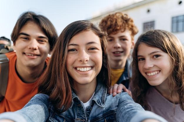 셀카를 찍는 귀엽고 아름다운 십대들. 친절한 그룹 아이들은 야외에서 셀카를 찍습니다.