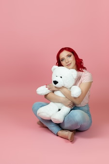 Cute, beautiful woman in jeans with red hair hugs a large white teddy bear sitting on the floor
