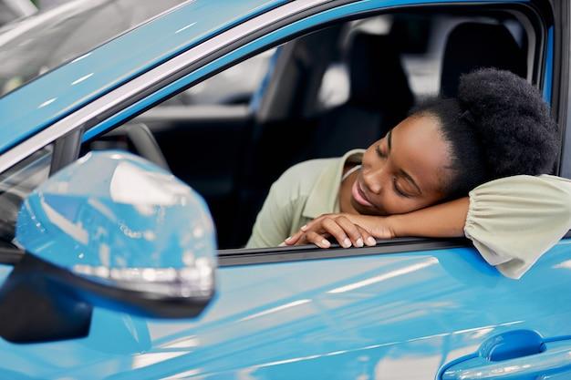 かわいい美しい女性が車に寄りかかった