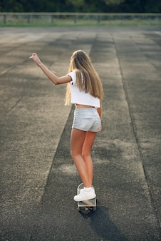 Cute beautiful young teen woman in a white t-shirt, short shorts and white sneakers ride a skateboard