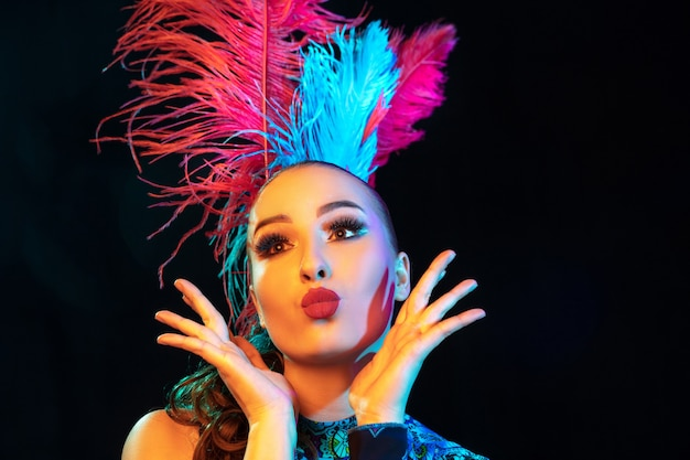 Cute. beautiful young woman in carnival, stylish masquerade costume with feathers on black wall in neon light. copyspace for ad. holidays celebration, dancing, fashion. festive time, party.