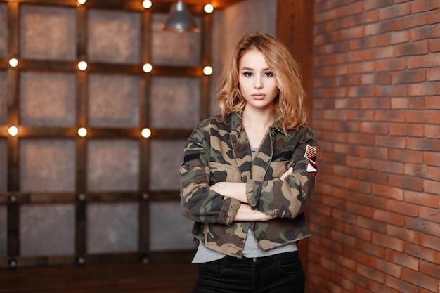 レンガの壁とライトの近くのモダンなスタジオでポーズをとる灰色のtシャツと黒のトレンディなジーンズのスタイリッシュなミリタリー迷彩ヴィンテージジャケットのかわいい美しい若い女性。魅力的なブロンドの女の子