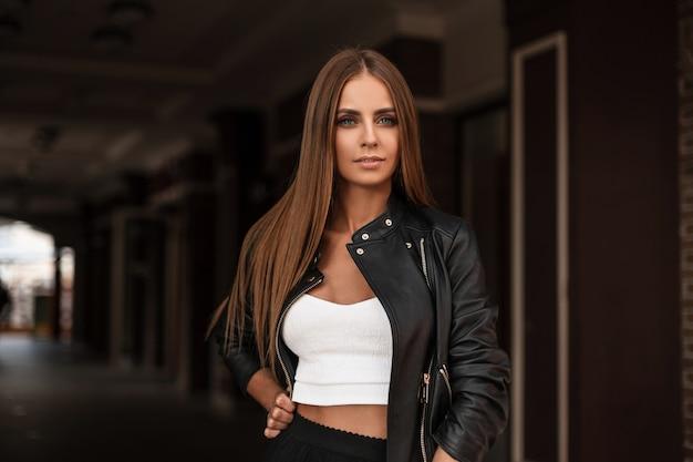 트렌디 한 탑에 세련된 블랙 재킷에 갈색 머리를 가진 자연스러운 메이크업으로 귀여운 아름다운 젊은 여성이 빈티지 건물 근처의 도시에 서 있습니다. 어두운 골목에서 포즈 예쁜 여자 패션 모델.