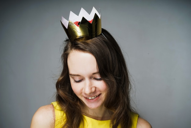 Cute beautiful young woman in a yellow dress smiling, on her head a golden crown