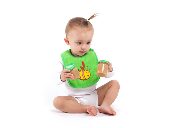 Cute beauty little girl in green bib hold baby food
