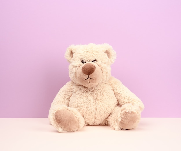 Cute beige teddy bear sitting on purple background, sad